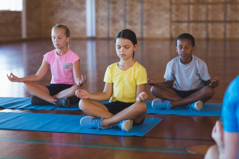 Image of children doing yoga, we provide yoga sessions which provides many benefits including cognitive development, self-esteem and determination.