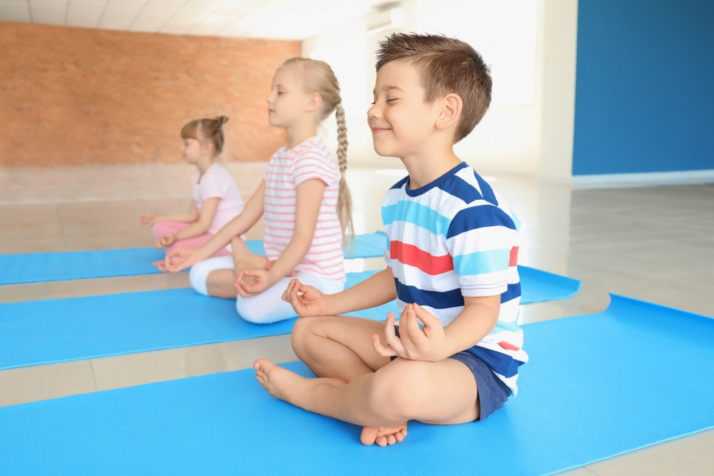 An image of children doing some meditation, Little Sunshine provide children with emotional development in the classroom.