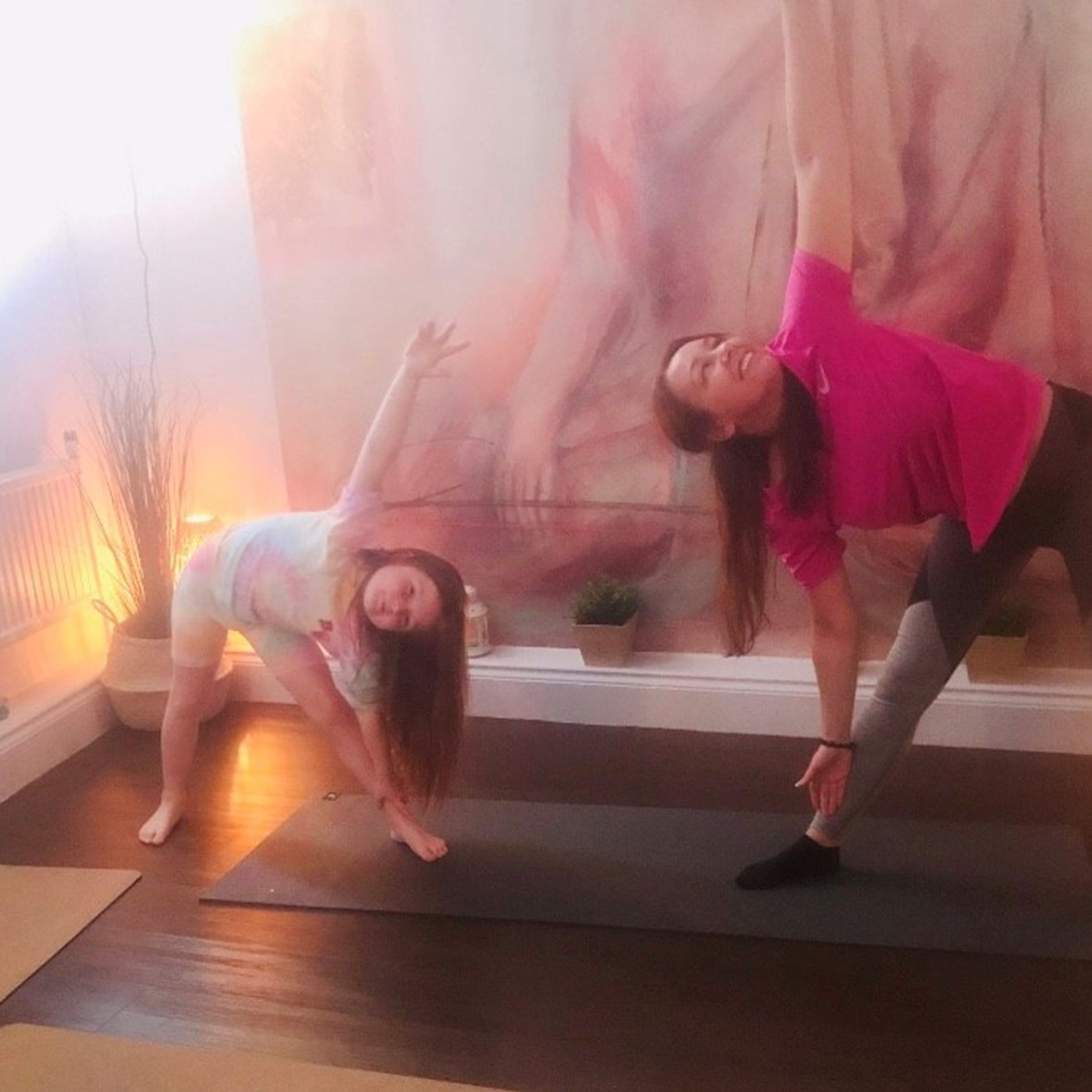 An image of Katie and a Child doing yoga that Little Sunshine provide to help wellbeing and improve self esteem.